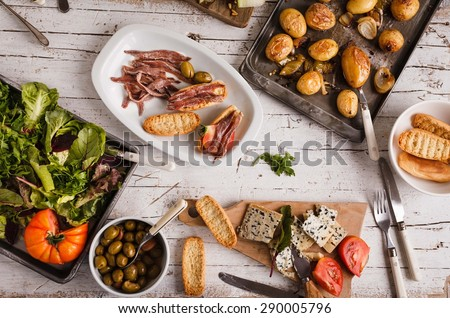 Spanish traditional dinner or lunch with fresh vegetables, blue cheese, grilled potatoes and sandwich with sprats marinated served over white rustic table.  - stock photo