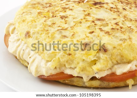 Spanish typical food. Spanish omelette stuffed with rice cream and tomato. Made with potatoes, onion and olive oil.