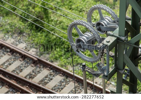 Spanner from overhead wiring, near a train track.  - stock photo