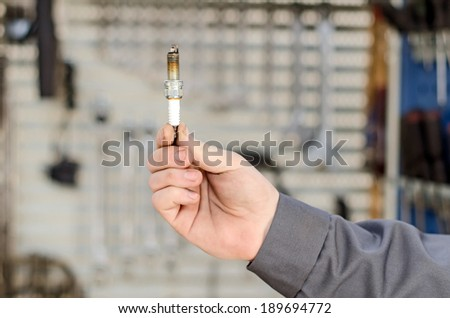 Spark plug in hand against the cabinet with tools. - stock photo