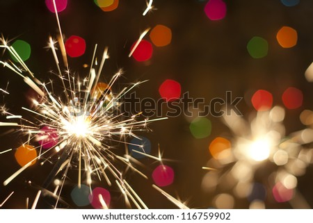 Sparkler and colorful bokeh christmas new year background - stock photo