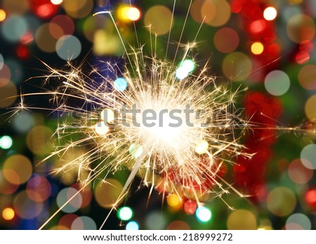 sparkler burning on background decorated Christmas tree  - stock photo
