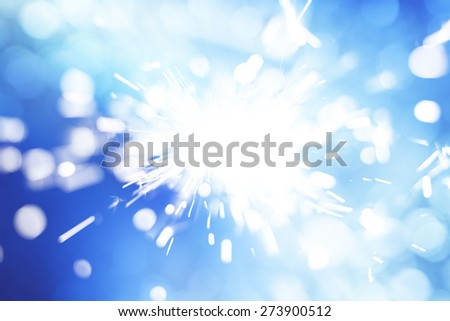 Sparkler infront of blue background - stock photo
