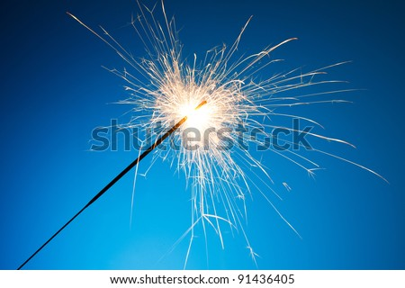 Sparkler on blue background - stock photo