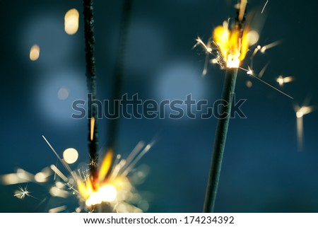 Sparklers burning in the dark at night with bright sparks and flame - stock photo
