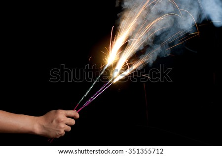 sparklers in hands on black background - stock photo