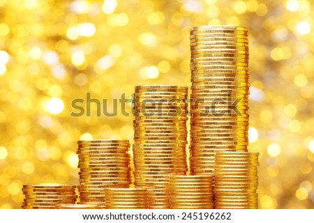 Sparkling new golden coins stacks on bright light glowing bokeh background, business finance wealth and success concept - stock photo