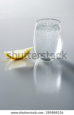 Sparkling water in  glass with lemon - stock photo