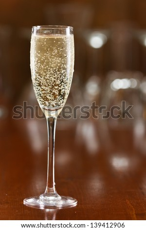 sparkling wine served in a flute on a out of focus bar top - stock photo