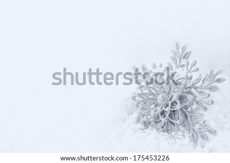 Sparkly Winter or Christmas or New Years Snowflake Ornament in Snow with Background Room or Space for Copy, your Words or Text.  Black and white with blue tone. - stock photo