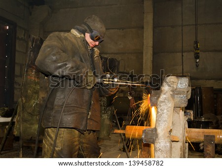 Sparks and drops of molten metal during work of welder.