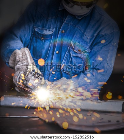 sparks while grinding in a steel factory  - stock photo