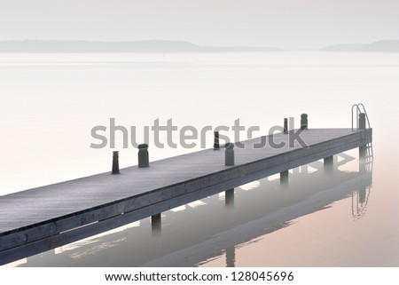 Sparse image of jetty in foggy lake - stock photo