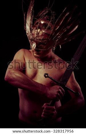 Spartan, warrior with golden mask and huge iron sword, body covered with gold dust - stock photo