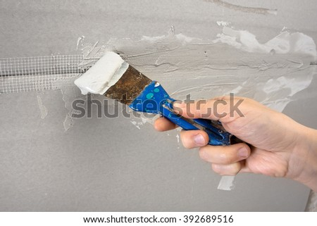 spatula with plaster in hand during plastering walls - stock photo