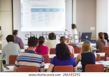Speaker giving presentation in lecture hall at university. Participants listening to lecture and making notes. - stock photo