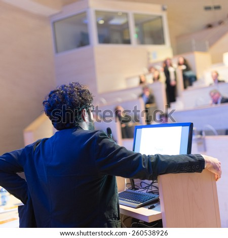Speaker giving talk on podium at Business Conference. Business and Entrepreneurship. Expert presenting his work in lectures hall. - stock photo