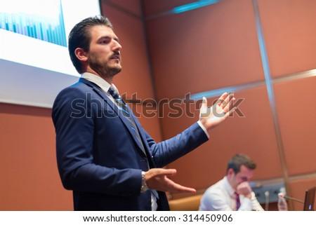 Speaker giving talk on podium at Business Conference. Entrepreneurship club. Horizontal composition.  - stock photo
