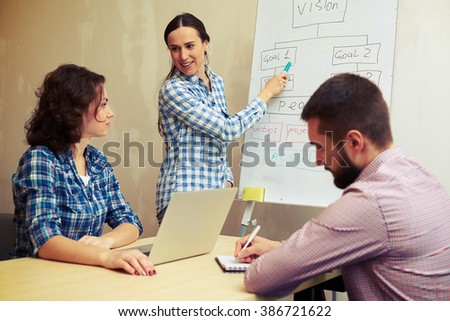 speaker pointing at flowchart and looking at colleagues in office - stock photo