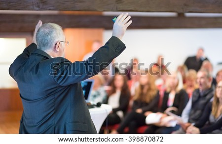 Speaker talking at Business Conference. Audience at the conference hall blured in background. Rear view. Horisontal composition. - stock photo
