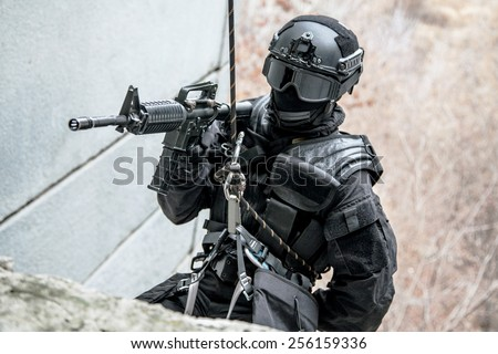 Spec ops police officer SWAT during rope exercises with weapons - stock photo
