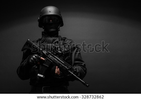 Spec ops police officer SWAT in black uniform studio  - stock photo