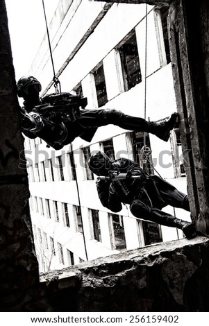 Spec ops police officers SWAT during rope exercises with weapons - stock photo
