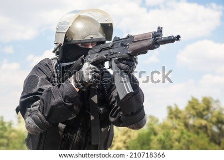 Spec ops soldier in black uniform and face mask with his rifle