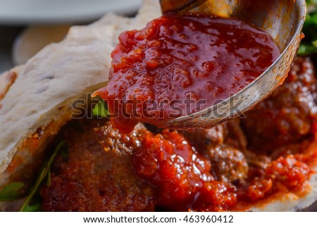 Special bailer for sauce is pouring tasty substance on the meatballs in the ciabatta. Rocket salad for better taste.