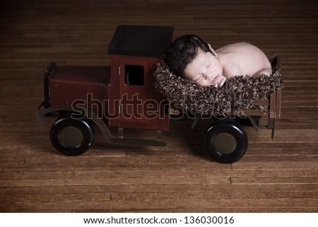 Special Delivery.  Adorable biracial newborn fast asleep in the back of a wooden toy truck. - stock photo