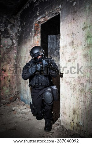 Special forces/ anti-terrorist police unit/private military contractor during night CQB hostage rescue raid/operation/mission (very harsh light for underline the atmosphere) - stock photo