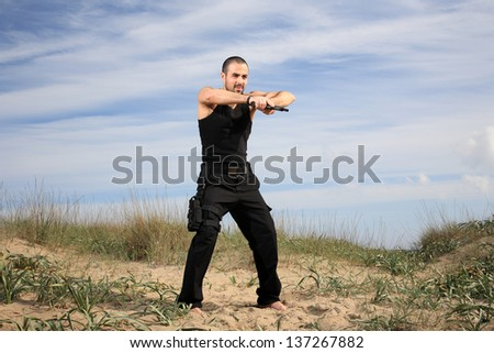special forces man at the beach holding a gun - stock photo