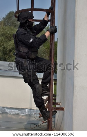 special forces officer climbs a ladder to the chimney, VIP protection, the observer - stock photo