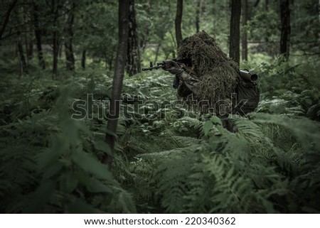 Special forces soldier dressed in ghillie camouflage with assault rifle on patrol - stock photo