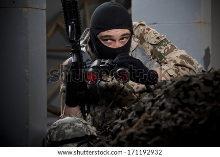 Special forces soldier with machine gun and binoculars hiding - stock photo