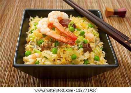 Special fried rice, or Yangchow fried rice, favourite Chinese food where barbecue pork, shrimp or prawn, onions and peas are added to fried rice cooked with egg. - stock photo