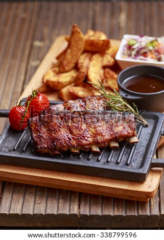 special marinated pork ribs with sauce and potatoes - stock photo