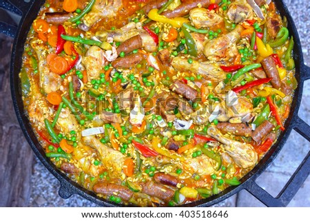 Special paella with sausage, meat, chicken, fish and different kinds of vegetables - stock photo