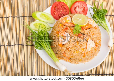 Special shrimp fried rice on white dish on wooden background - stock photo
