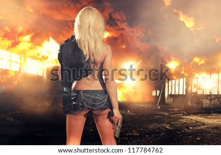 special tactics sexy woman holding up her weapon with explosion behind her - stock photo