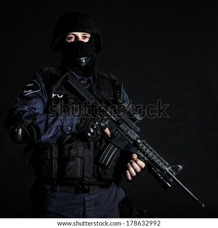 Special weapons and tactics (SWAT) team officer on black background - stock photo