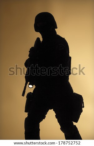 Special weapons and tactics team (SWAT) officer silouette in the fog - stock photo
