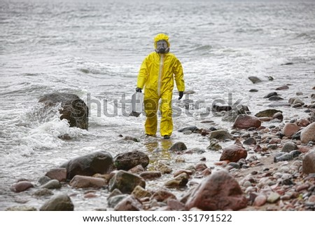 specialist in protective suit with silver suitcase walking on rocky beach in stormy day - stock photo