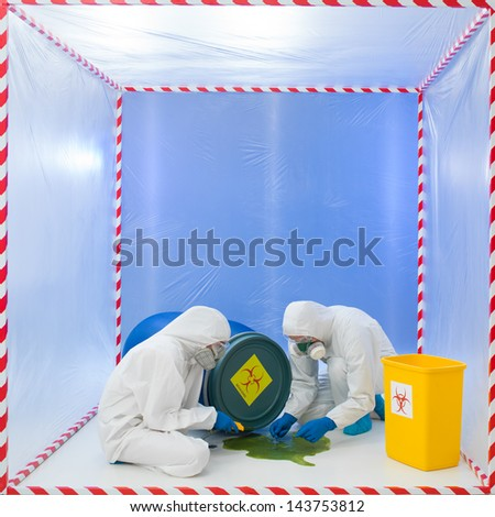 specialists wearind white protection suits and gas masks collecting samples from a liquid spilling from a blue biohazard barrel - stock photo