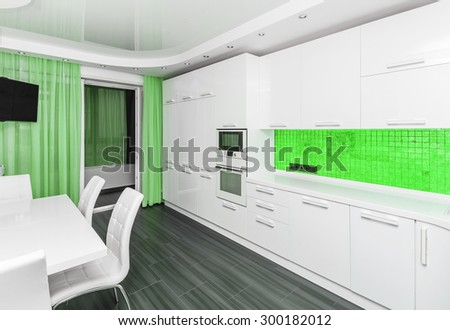 Specious modern white green interior kitchen-dining room with the built-in household appliances and the TV - stock photo