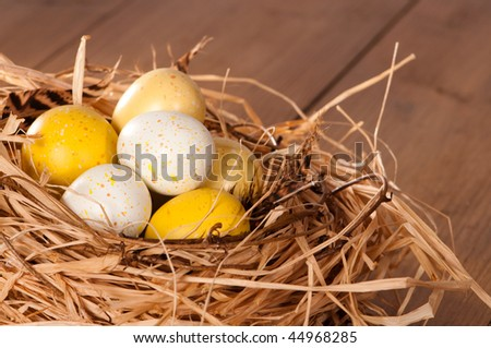 Speckled Easter eggs nestled in straw nest lined with feathers