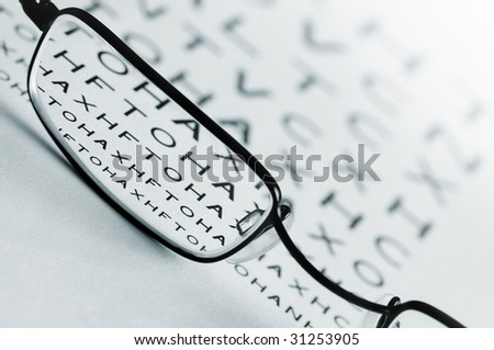 Spectacles bringing an eye test chart into focus. - stock photo