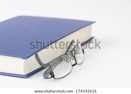 Spectacles next to closed book - stock photo