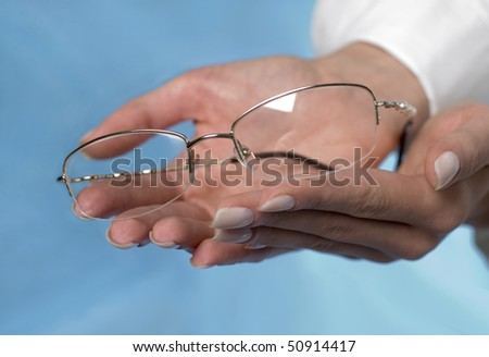 Spectacles on the feminine palms - stock photo