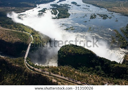 Spectacular aerial view of Victoria falls showing the Zambezi river in full flood and the bridge crossing - stock photo